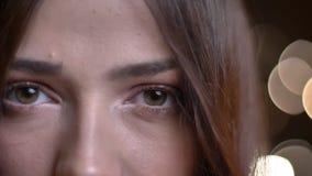 Closeupstående av den unga caucasian kvinnliga framsidan med gröna ögon som ser raka på kameran i begrundande lager videofilmer