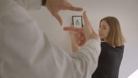 Closeupstående av den unga gladlynta parinflyttningen en ny slags tvåsittssoffa framlänges Kvinnligt rymma en bild och avgöra på  stock video