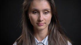 Closeupstående av den unga gulliga caucasian kvinnlign med brunetthår som ser ner i begrundande med isolerat royaltyfria foton