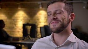 Closeupstående av den unga lyckliga caucasian affärsmannen som framme sitter av bärbara datorn och firar med triumf stock video
