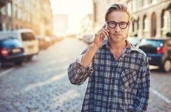 Closeupstående av den unga mannen som talar på hans mobiltelefon Royaltyfri Foto