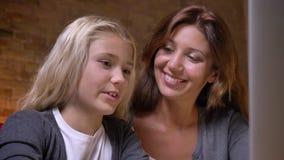 Closeupstående av den unga modern och lilla nätta flickan som tillsammans håller ögonen på en film på bärbara datorn Mamma som da stock video