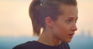 Closeupstående av den unga motiverade sportiga kvinnliga joggeren i en svart t-skjorta som värmer och ser upp det härligt arkivfilmer