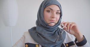 Closeupstående av den unga muslim attraktiva kvinnliga doktorn i hijab och det vita laget som ser kameran som rymmer glasögon arkivfilmer