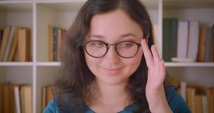 Closeupstående av den unga nätta caucasian kvinnliga studenten i exponeringsglas som ler med osäkerhet som ser kameran i stock video