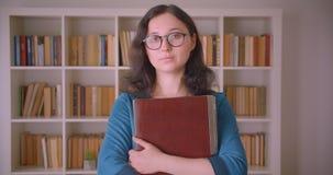Closeupstående av den unga nätta caucasian kvinnliga studenten i exponeringsglas som rymmer en bärbar dator som ser kameraanseend arkivfilmer