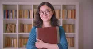 Closeupstående av den unga nätta caucasian kvinnliga studenten i exponeringsglas som rymmer en bärbar dator som ser kameran i hög arkivfilmer