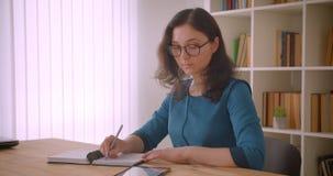 Closeupstående av den unga nätta caucasian kvinnliga studenten i exponeringsglas som studerar och skriver i använda för antecknin lager videofilmer