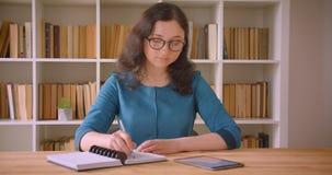 Closeupstående av den unga nätta caucasian kvinnliga studenten i exponeringsglas som studerar och skriver i använda för antecknin arkivfilmer