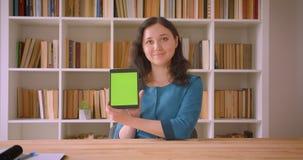 Closeupstående av den unga nätta caucasian kvinnliga studenten som använder minnestavlan och visar den gröna skärmen till kameran lager videofilmer