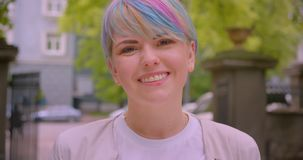 Closeupstående av den unga nätta caucasian kvinnlign med färgat hår som ler glatt se kameran utomhus i lager videofilmer
