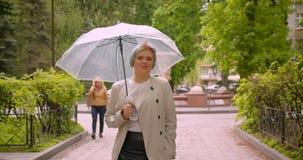 Closeupstående av den unga nätta caucasian kvinnlign med färgat hår som rymmer ett paraply som utomhus går in mot kamera in lager videofilmer