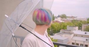 Closeupstående av den unga nätta caucasian kvinnlign med färgat hår som rymmer ett paraply som utomhus väntar på för hennes pojkv stock video