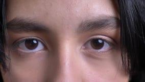 Closeupstående av den unga nätta caucasianen som är kvinnlig med bruna ögon som ser raka på kameran i begrundande lager videofilmer