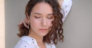 Closeupstående av den unga nätta långa haired lockiga caucasian kvinnliga modellen som framme poserar av kameran med bakgrund arkivfilmer