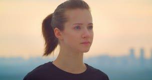 Closeupstående av den unga nätta sportiga kvinnliga joggeren i en svart t-skjorta som utomhus ser den härliga solnedgången lager videofilmer