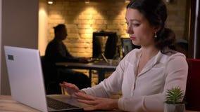 Closeupstående av den unga uttråkade caucasian kvinnliga kontorsarbetaren som är inte vetgirig och inomhus använder bärbara dator lager videofilmer