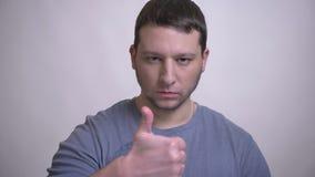 Closeupstående av den vuxna attraktiva caucasian mannen som gör en gest en tumme upp uppvisning av godtagande som ser kameran med stock video