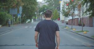 Closeupstående av den vuxna caucasian idrotts- manliga joggeren som utomhus går ner gatan i den stads- staden lager videofilmer