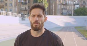 Closeupstående av den vuxna caucasian sportiga manliga joggeren som ser kameran som står på stadion i den stads- staden stock video