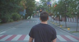 Closeupstående av den vuxna caucasian sportiga manliga joggeren som utomhus går ner gatan i den stads- staden stock video