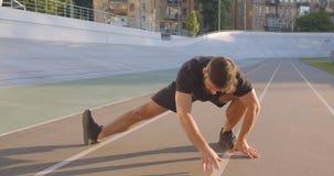 Closeupstående av den vuxna caucasian sportiga manliga joggeren som utomhus värmer stadion i den stads- staden upp stock video