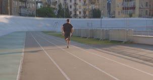 Closeupstående av den vuxna caucasian sportiga manliga löparen som utomhus värmer upp och joggar på stadion i den stads- staden stock video