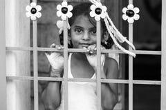 Closeupstående av det blyga blyga unga nätta indiska flickabarnet som ser bort och bak porten svart isolerad begreppsfrihet fotografering för bildbyråer