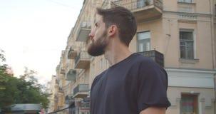 Closeupstående av det vuxna caucasian sportiga manliga joggeranseendet på gatan i den stads- staden utomhus lager videofilmer