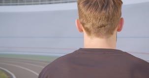 Closeupstående av det vuxna caucasian sportiga manliga joggeranseendet på stadion i den stads- staden utomhus arkivfilmer
