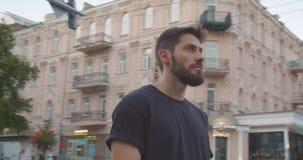 Closeupstående av det vuxna caucasian sportiga manliga löpareanseendet på gatan i den stads- staden utomhus lager videofilmer