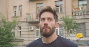 Closeupstående av det vuxna caucasian sportiga skäggiga manliga löpareanseendet på gatan i den stads- staden utomhus lager videofilmer