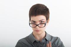 Closeupstående av en allvarlig härlig kvinna som lyfter ett ögonbryn - som isoleras på vit bakgrund Royaltyfri Fotografi