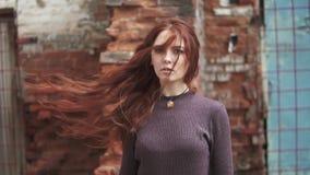 Closeupstående av en härlig rödhårig flicka fladdrande hårwind eyes den mystiska flickan långsam rörelse lager videofilmer