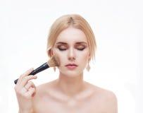 Closeupstående av en kvinna som applicerar det torra kosmetiska tonala fundamentet på framsidan Arkivfoto
