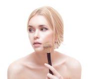 Closeupstående av en kvinna som applicerar det torra kosmetiska tonala fundamentet på framsidan Royaltyfria Bilder