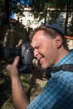Closeupstående av en manlig turist- fotograf med en judisk hatt som rymmer en kamera som tar ett skott arkivfoton