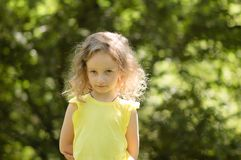 Closeupstående av en skeptisk liten flicka som suspiciously som ser är skeptisk, halva-leende, ironiskt grön stående Arkivbilder