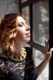 Closeupstående av en trevlig kvinnlig med stängda ögon som står nära det hemmastadda fönstret och tycker om varmt solljus arkivbild