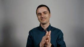 Closeupstående av en ung affärsman som approvingly ler och applåderar händer lager videofilmer