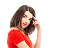Closeupstående av en ung brunettflicka i den röda t-skjortan som ser in i kameran mot vit bakgrund royaltyfria bilder