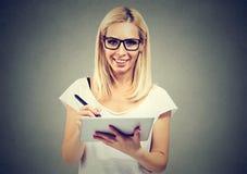 Closeupstående av en ung kvinna som arbetar med nålen och digital minnestavlaPC arkivbild