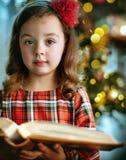 Closeupstående av ett gulligt, liten flicka som rymmer en bok royaltyfri fotografi