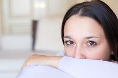 Closeupstående av frustrerat sammanträde för ung kvinna på soffan arkivbild