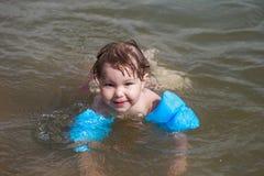 Closeupstående av gullig liten flickasimning, lyckligt barn som har gyckel i vatten royaltyfria foton