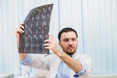 Closeupstående av intellektuella mansjukvårdpersonaler med vit labcoat som ser radiographic bild för hjärnröntgenstråle Arkivfoto