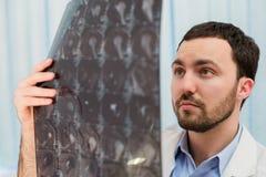 Closeupstående av intellektuella mansjukvårdpersonaler med vit labcoat som ser radiographic bild för hjärnröntgenstråle Arkivbilder