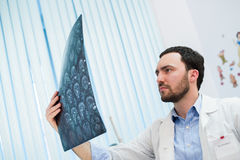 Closeupstående av intellektuella mansjukvårdpersonaler med vit labcoat som ser radiographic bild för hjärnröntgenstråle Fotografering för Bildbyråer