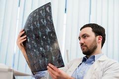 Closeupstående av intellektuella mansjukvårdpersonaler med vit labcoat som ser radiographic bild för hjärnröntgenstråle Royaltyfria Bilder