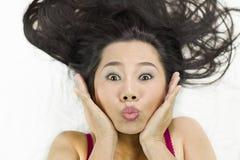 Closeupstående av lyckliga asiatiska kvinnor som ligger på jordning med svart långt hår tillförordnat leende, gyckel royaltyfri bild